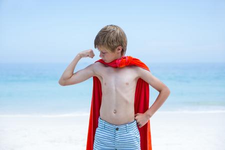 niño sin camisa: muchacho sin camisa en traje de superhéroe flexionar los músculos en la playa