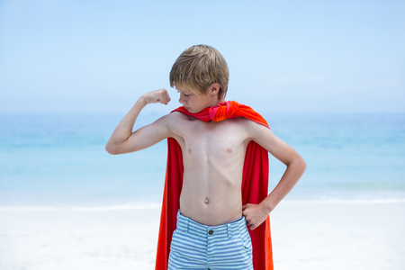 flexing: Shirtless boy in superhero costume flexing muscles at beach Stock Photo