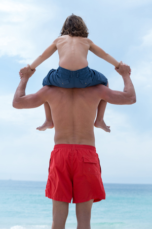 shoulder carrying: Rear view of man carrying son on shoulder at beach