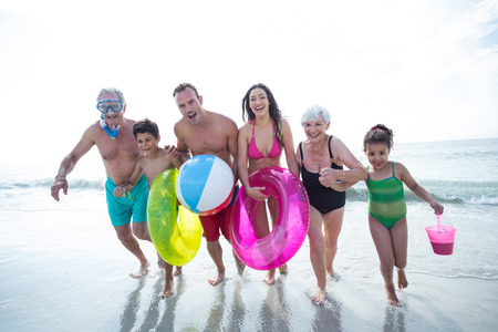 Happy multi-generation family running on sea shore at beach