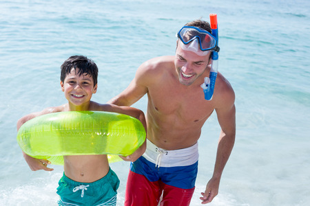 away from it all: Happy family with swimming ring standing in sea at beach Stock Photo