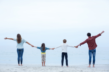 away from it all: Rear view of family holding hands while standing at sea shore against sky Stock Photo