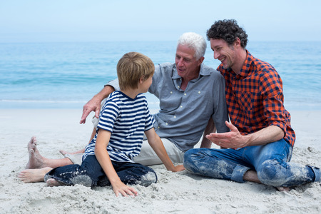 multigeneration: Multi-generation family smiling while resting at sea shore