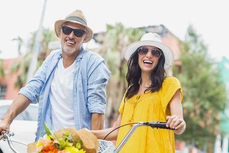 ciclos: Retrato de pareja feliz con ciclos de pie al aire libre