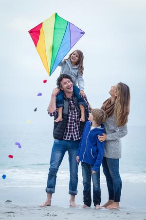 In voller Länge von fröhlichen Familie mit dem Kite am Meer Ufer stehen