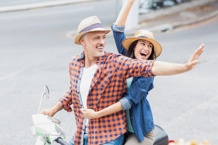 city life: Excited couple waving hands on moped while riding in city