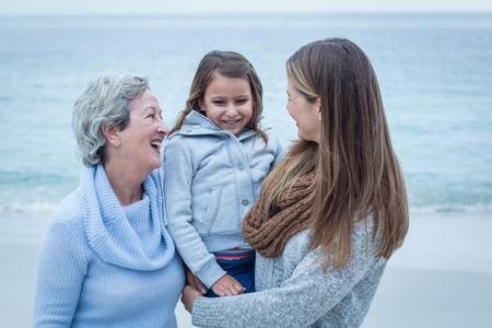three generations of women: Smiling three generations of women standing at beach Stock Photo
