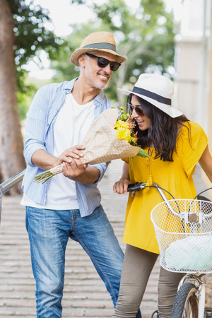 smelling: Woman smelling flower with man standing outdoors Stock Photo