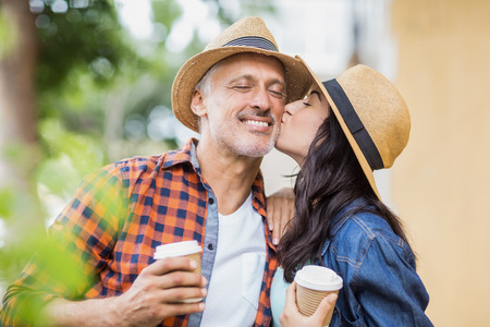 cheek to cheek: Woman kissing on mans cheek while holding coffee cup