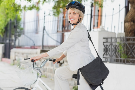 executive helmet: Portrait of businesswoman with helmet sitting on cycle in city