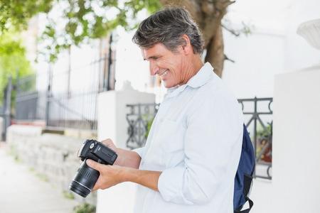 looking into camera: Happy man looking into camera in city