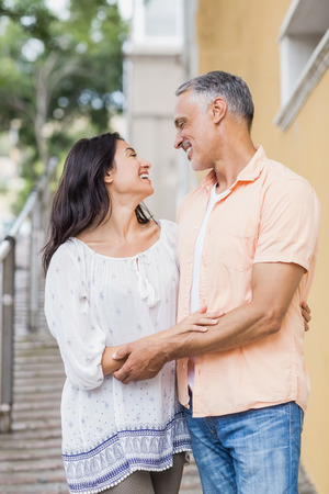 Cheerful couple looking each other while standing against building in city