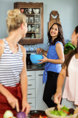 preparing food: Female friends laughing while preparing food in kitchen at home Stock Photo
