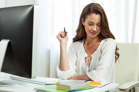 mujeres morenas: Empresaria feliz trabajando en escritorio en la oficina