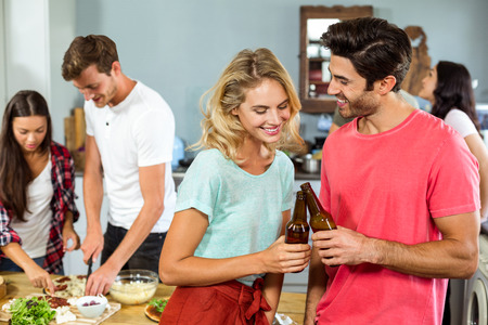 thirties: Smiling young couple toasting beer bottles with friend in background at home