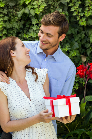 front yard: Romantic man giving gift to woman at front yard