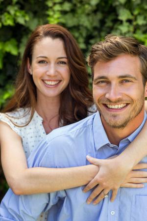 front yard: Young smiling woman hugging man at front yard Stock Photo