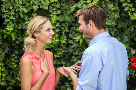 front yard: Happy romantic man wearing ring to woman at front yard
