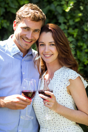 front yard: Portrait of romantic couple holding wineglasses at front yard