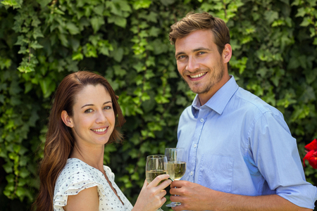 front yard: Portrait of happy couple toasting wineglasses at front yard