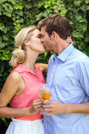 front yard: Happy couple kissing while toasting wineglasses at front yard Stock Photo