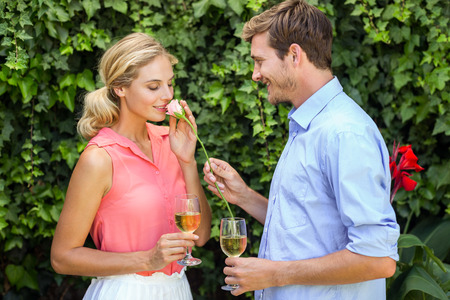 front yard: Young man giving flower to woman while holding wineglasses at front yard
