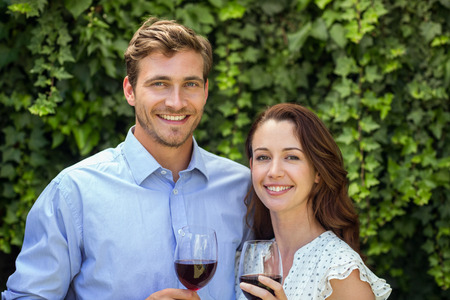 front yard: Portrait of happy couple holding wineglasses at front yard