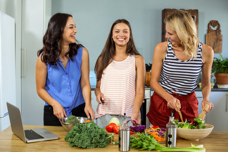 preparing food: Happy female friends enjoying while preparing food in kitchen at home