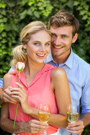 front yard: Portrait of happy man giving flower to woman while holding wineglasses at front yard
