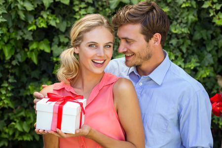 front yard: Romantic man giving gift to surprised woman at front yard