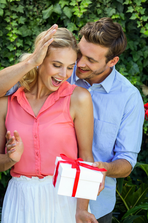 front yard: Romantic happy man giving gift to woman at front yard