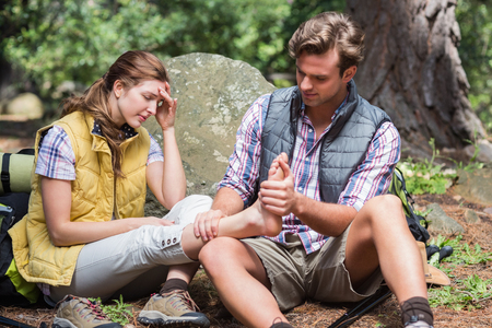calf strain: Man massaging leg of woman while sitting on field during hiking