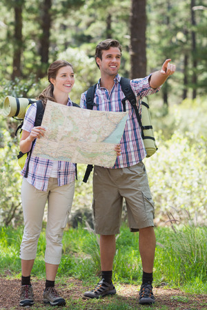 young tree: Young couple pointing and planning with map during hiking in forest