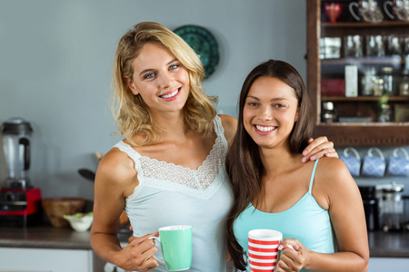 kitchen counter: Portrait of happy female friends holding coffee cups in kitchen at home Stock Photo