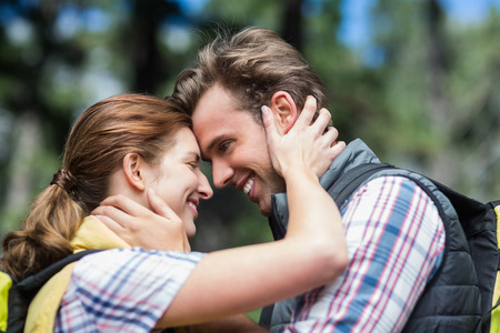 adventuring: Smiling couple looking face to face during hiking in forest Stock Photo