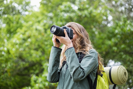 looking through an object: Low angle view of woman photographing with camera in forest Stock Photo