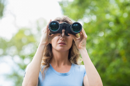 looking through an object: Close-up of woman looking through binocular in forest