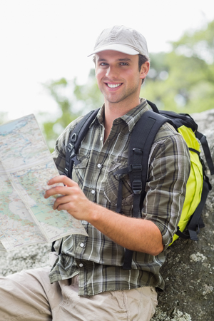 adventuring: Portrait of happy young hiker with map against rock