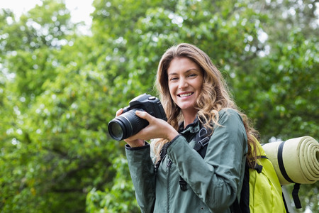 adventuring: Portrait of happy woman with camera during hiking Stock Photo