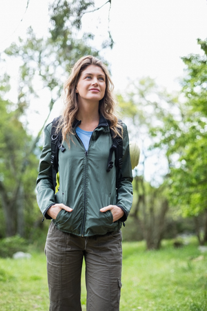 hands on pockets: Beautiful woman with hands in pockets standing in forest Stock Photo