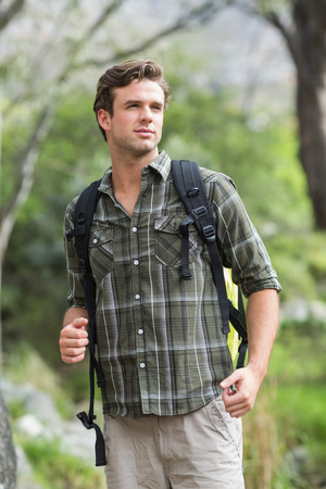 adventuring: Young hiker looking away while standing in forest