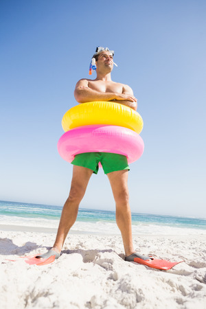 rubber ring: Smiling man posing with rubber ring on the beach