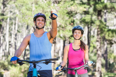 causal clothing: Young man with woman pointing while riding bicycle at forest Stock Photo