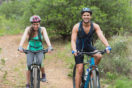 dirt road recreation: Portrait of couple riding bicycles on dirt road in forest Stock Photo