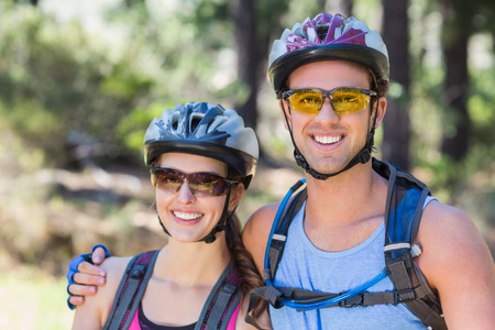 causal clothing: Portrait of smiling young couple wearing helmets at forest