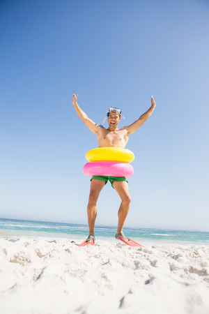 escapism: Smiling man posing with rubber ring on the beach