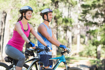 causal clothing: Happy man and woman riding bicycle against trees at forest