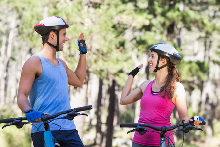causal clothing: Young couple giving high five while riding bicycle at forest