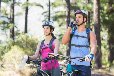 causal clothing: Adventurous young couple with bicycle at forest