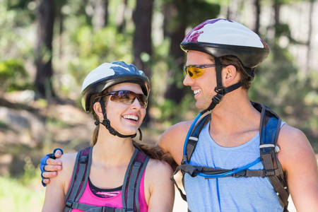 causal clothing: Happy young couple wearing helmets against tree at forest